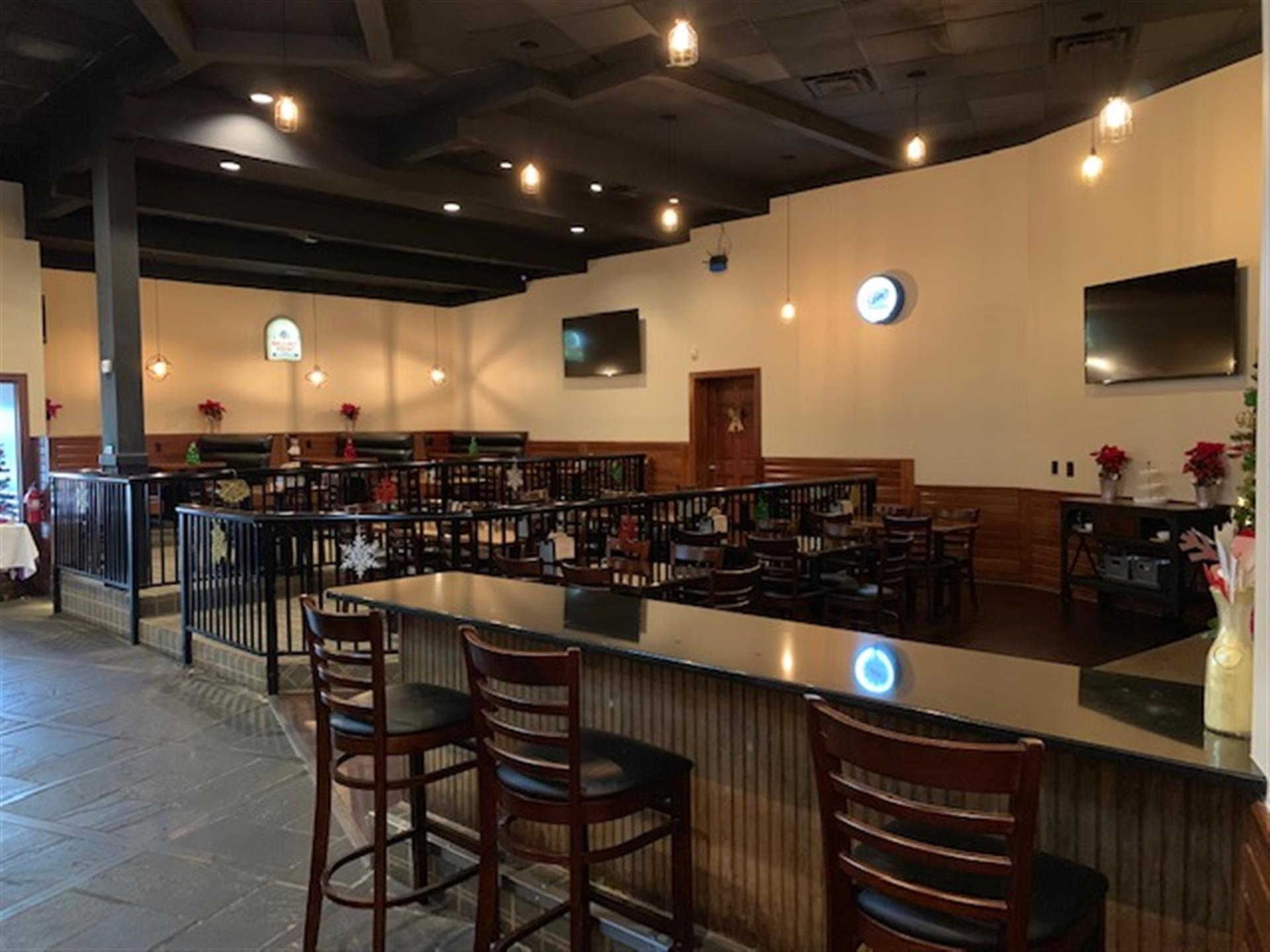 the bar area of the event space with three stools at the bar and the tables and chairs in the background with two flat screen tvs on the walls