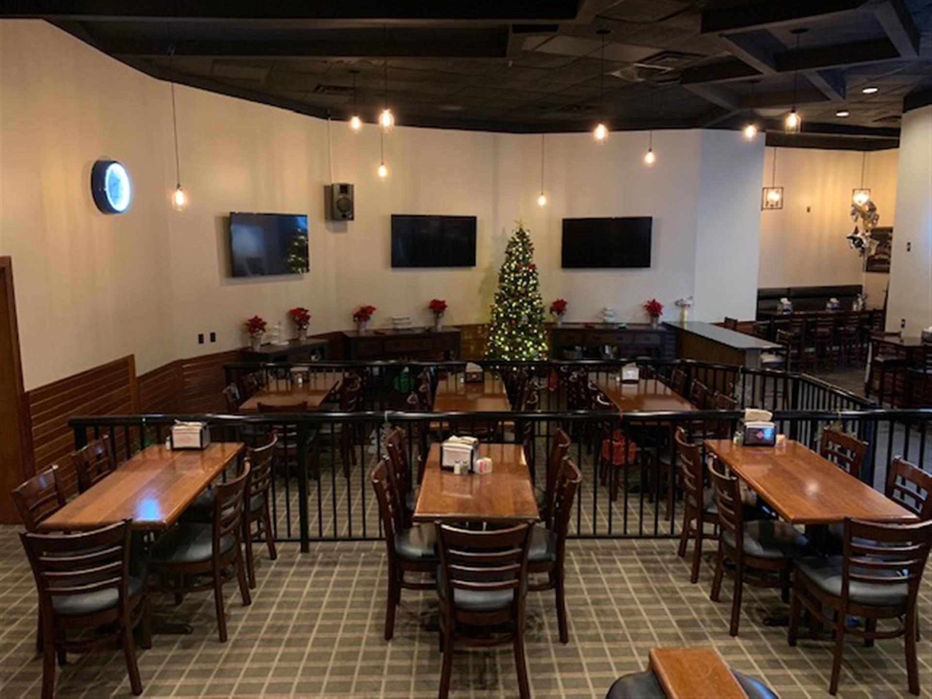 event space with six tables in view with five chairs at each table with three flat screen tvs on the wall and a christmas tree in the background