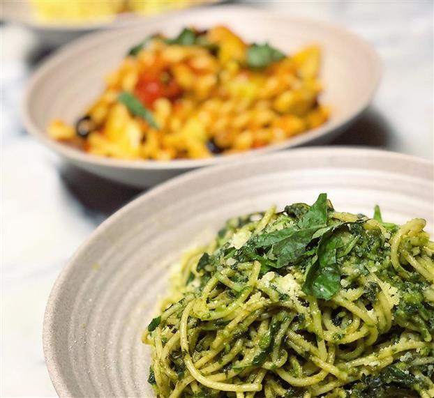 spaghetti with pesto sauce and fresh basil with a pasta and red sauce dish in the background