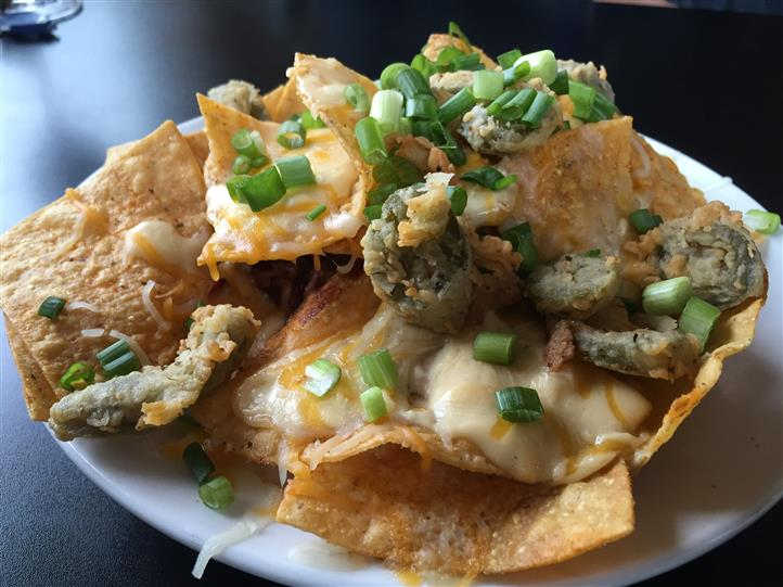 Nachos covered with cheese sauce and fried peppers topped with green onions