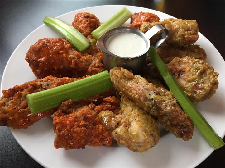 Deep fried wings served with dipping sauce and celery sticks