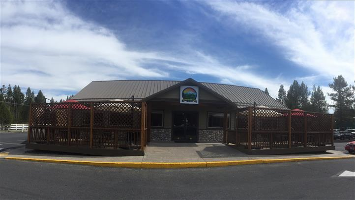 Photo of the restaurant from the outside with a blue sunny sky and trees in the background