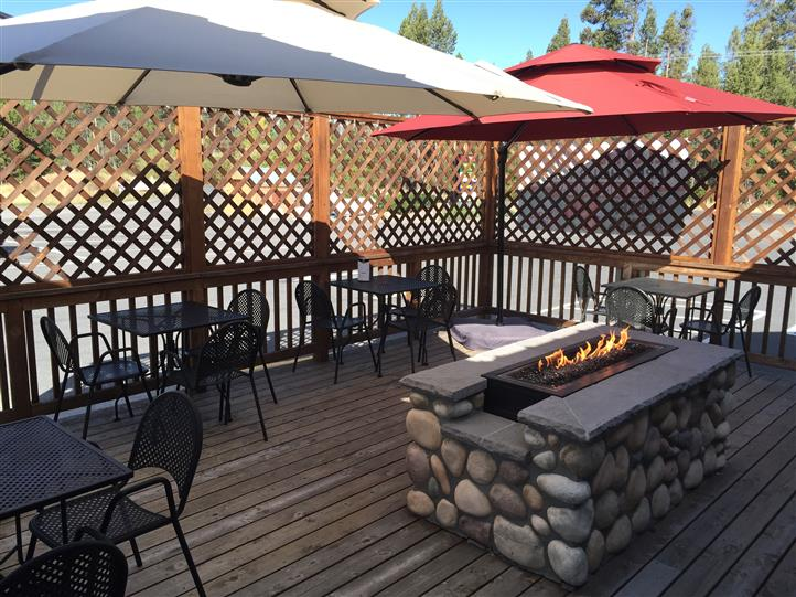 Outdoor patio with a stone wall fireplace in the middle and large umbrellas shading the tables