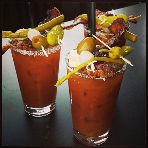 Three tall glasses with Bloody Mary cocktails topped with crispy bacon, pepperoncini, green olives and cheese bites