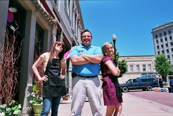 three employees posing outside the coffee house