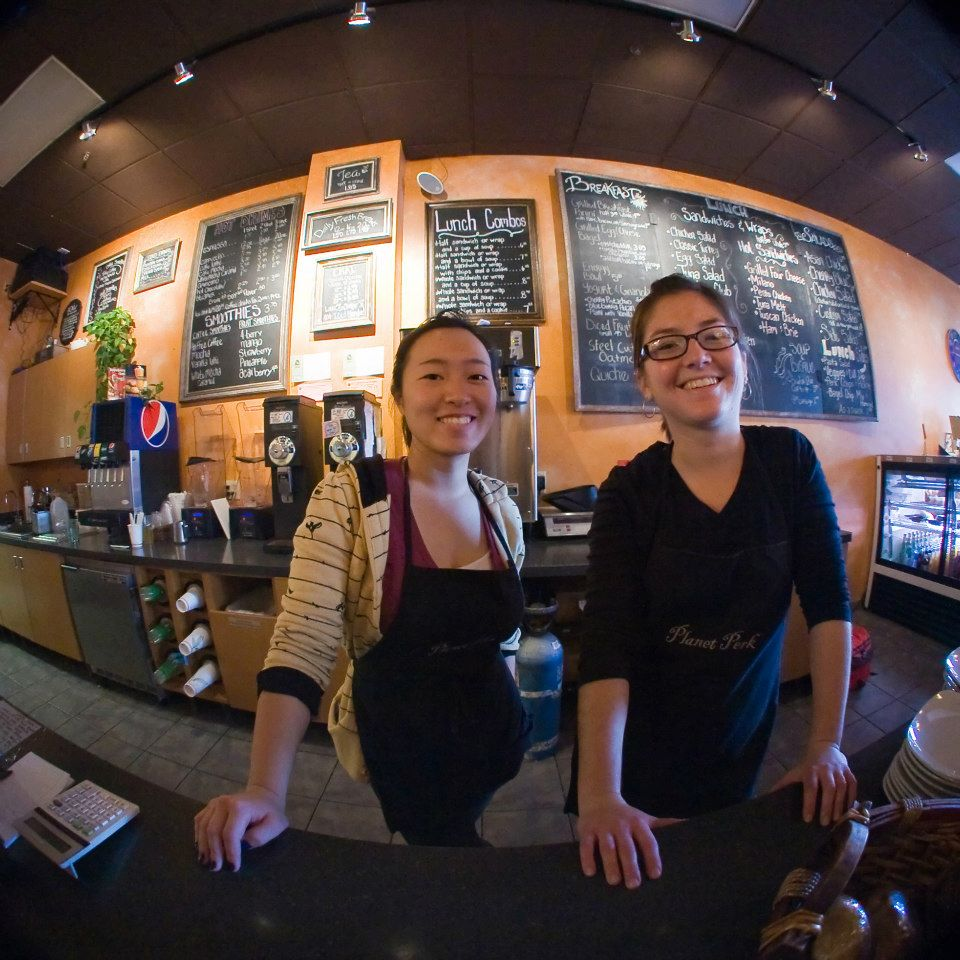 two baristas smiling through a fisheye lens