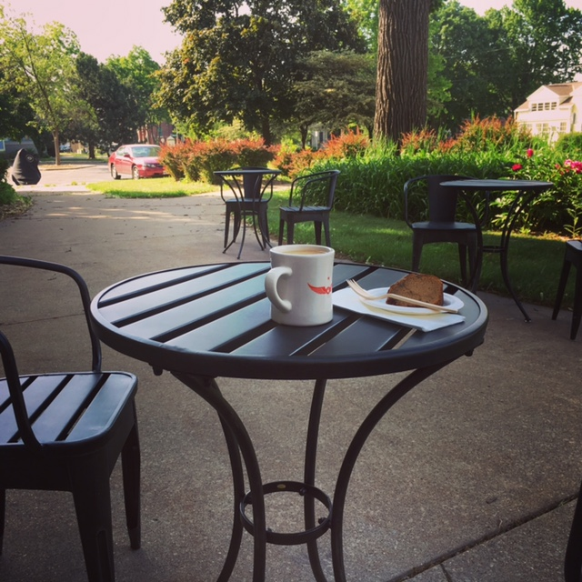 outdoor seating; coffee and a pastry on a cafe table at the grind location