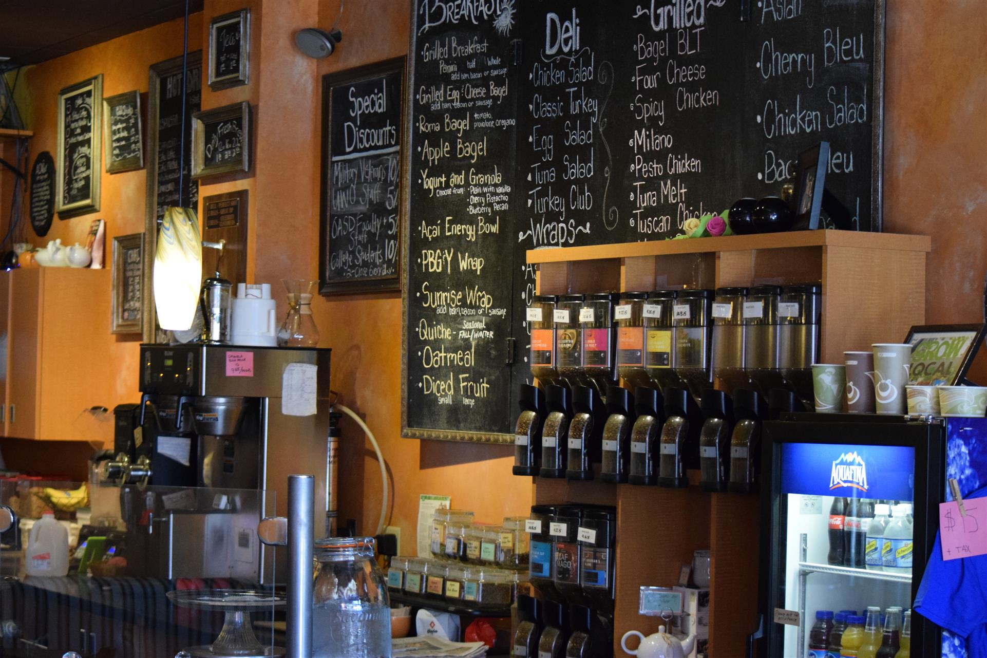 view of behind the counter of the chalkboard menu and drink supplies