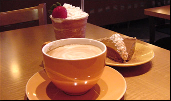 hot latte in a cup with a saucer, with a fruit smoothie and slice of pie in the background