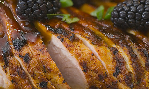 a close up shot of a golden brown chicken with blackberries