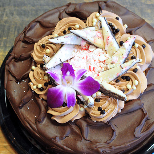 A chocolate cake with peppermint bark and a decorative flower on top