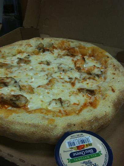 A round pizza with melted mozzarella and meat with a side of ranch dressing