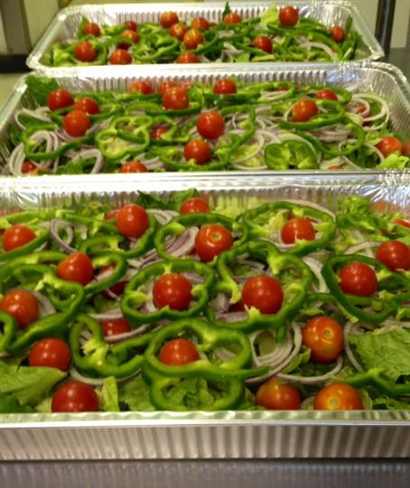 House salad in to-go containers with cherry tomatoes, green peppers, and red onion