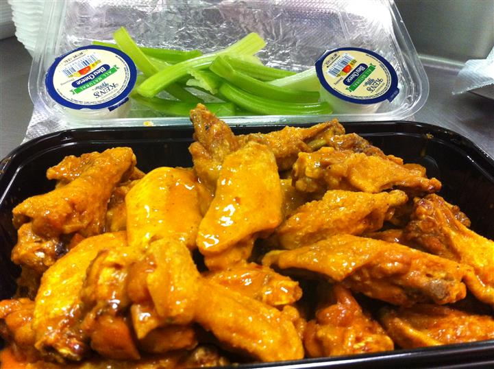 Buffalo wings in a to-go container with celery and ranch dressing on the side