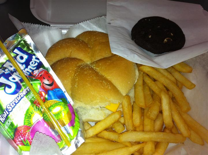 A cheeseburger with french fries, a cookie, and a kool aid juice box on the side