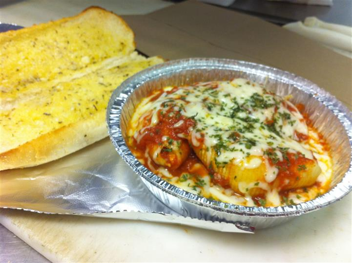 Open garlic bread toasted next to a to-go container of Chicken Parmesan different angle