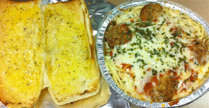 Open garlic bread toasted next to a to-go container of meatballs, tomato sauce, and melted mozzarella on top from  different angle
