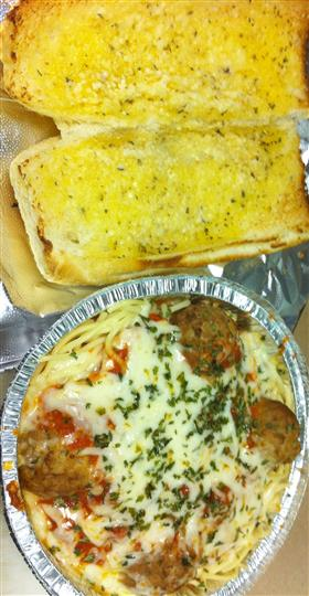 Open garlic bread toasted next to a to-go container of meatballs, tomato sauce, and melted mozzarella on top from a different angle