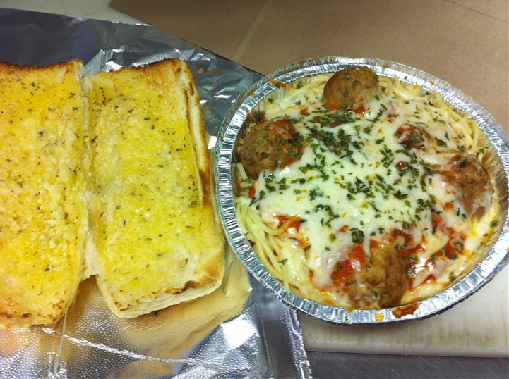 Open garlic bread toasted next to a to-go container of meatballs, tomato sauce, and melted mozzarella on top