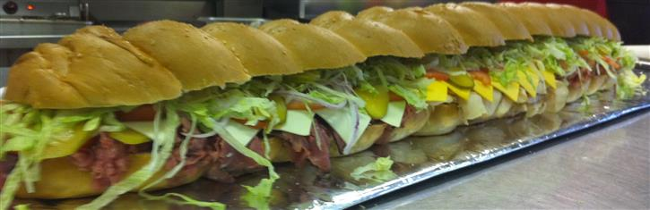 A giant hero with shredded lettuce, tomatoes, red onion, paresan cheese and meats