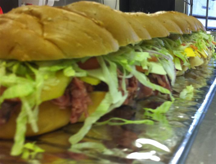 An italian hero with roast beef, shredded lettuce, banana peppers, and parmesan cheese