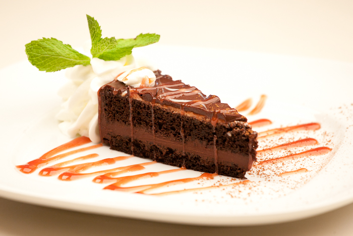Chocolate cake served with white cream and cherry syrup
