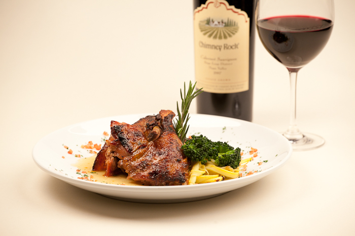 A meat dish served with lasagna and broccoli with a bottle and a glass of red wine