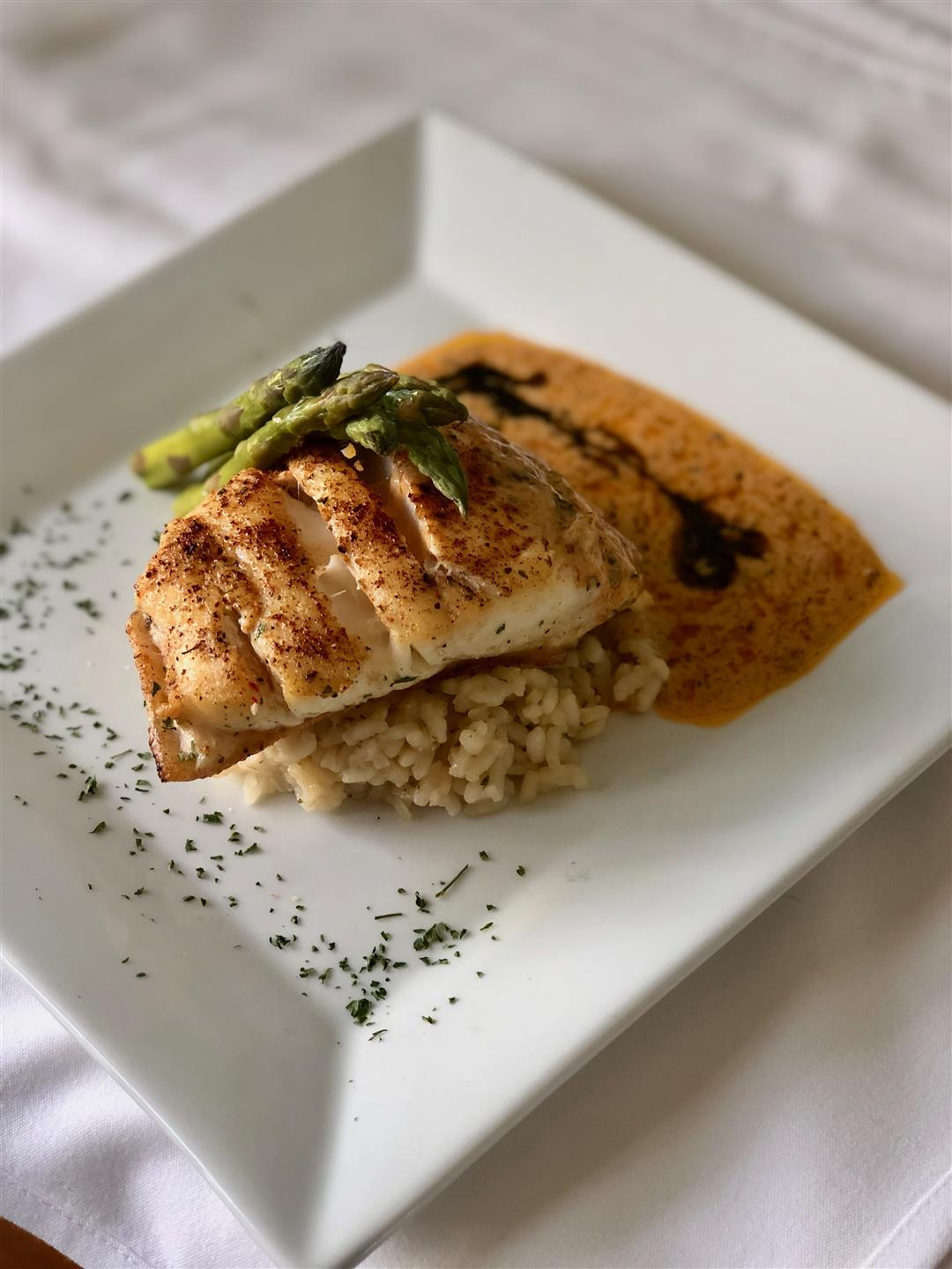 PARMESAN COD: tomato chive buerre blanc, risotto, and vegetables