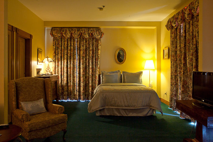 room with a queen bed and a chair