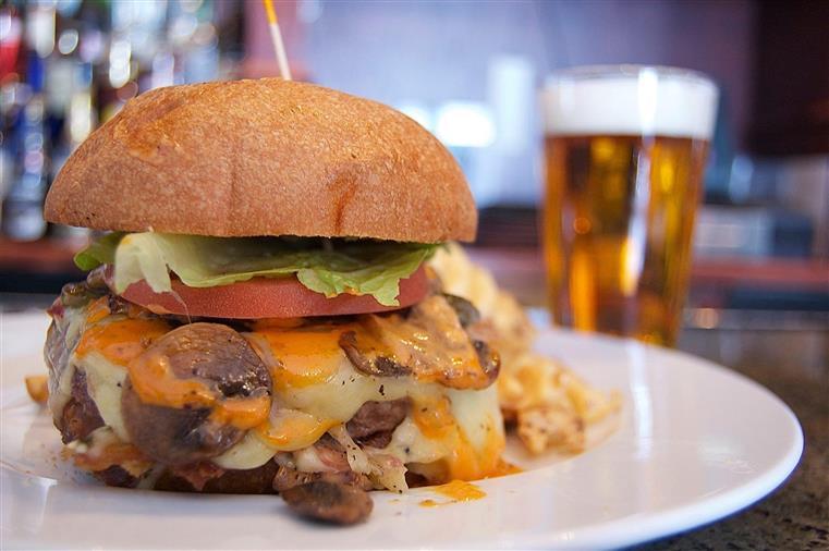 cheeseburger with mushrooms and a glass of beer