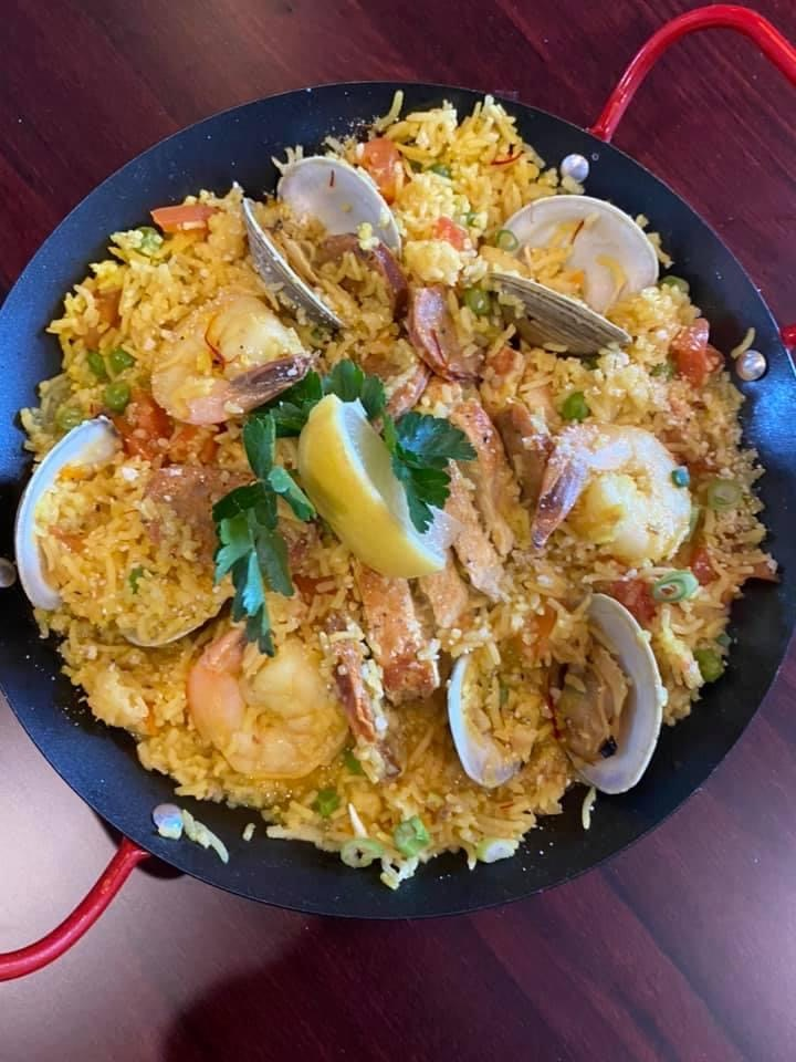 SEAFOOD PAELLA: mussles, clams, shrimp, chicken, chorizo, english peas, & roasted tomatoes over saffron rice