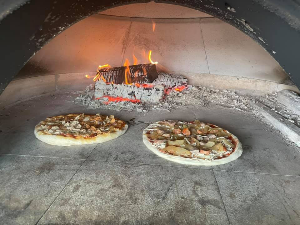 wood fired oven cooking two pizzas