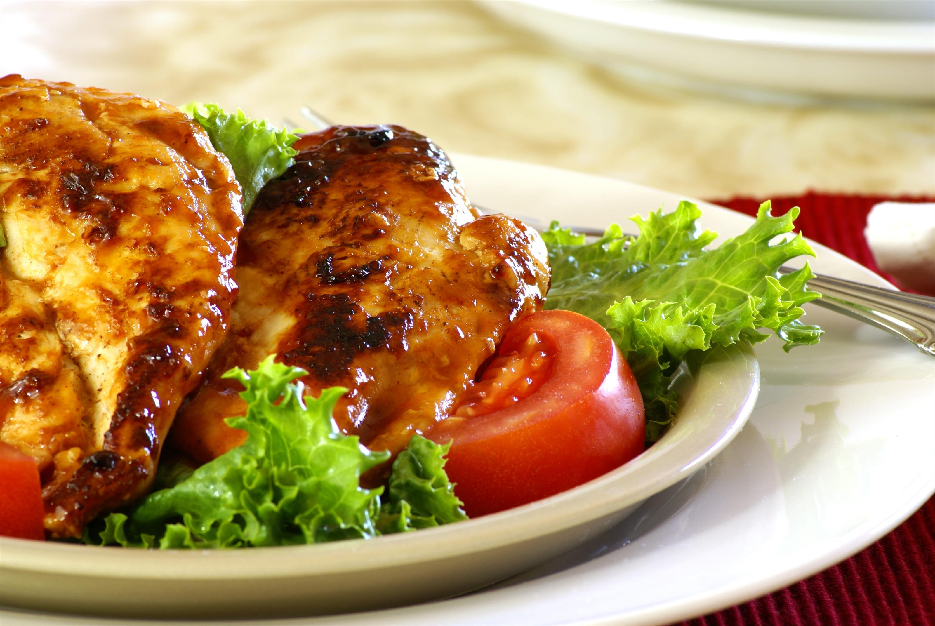 Two pieces of chicken breast with over lettuce and tomato on white dish