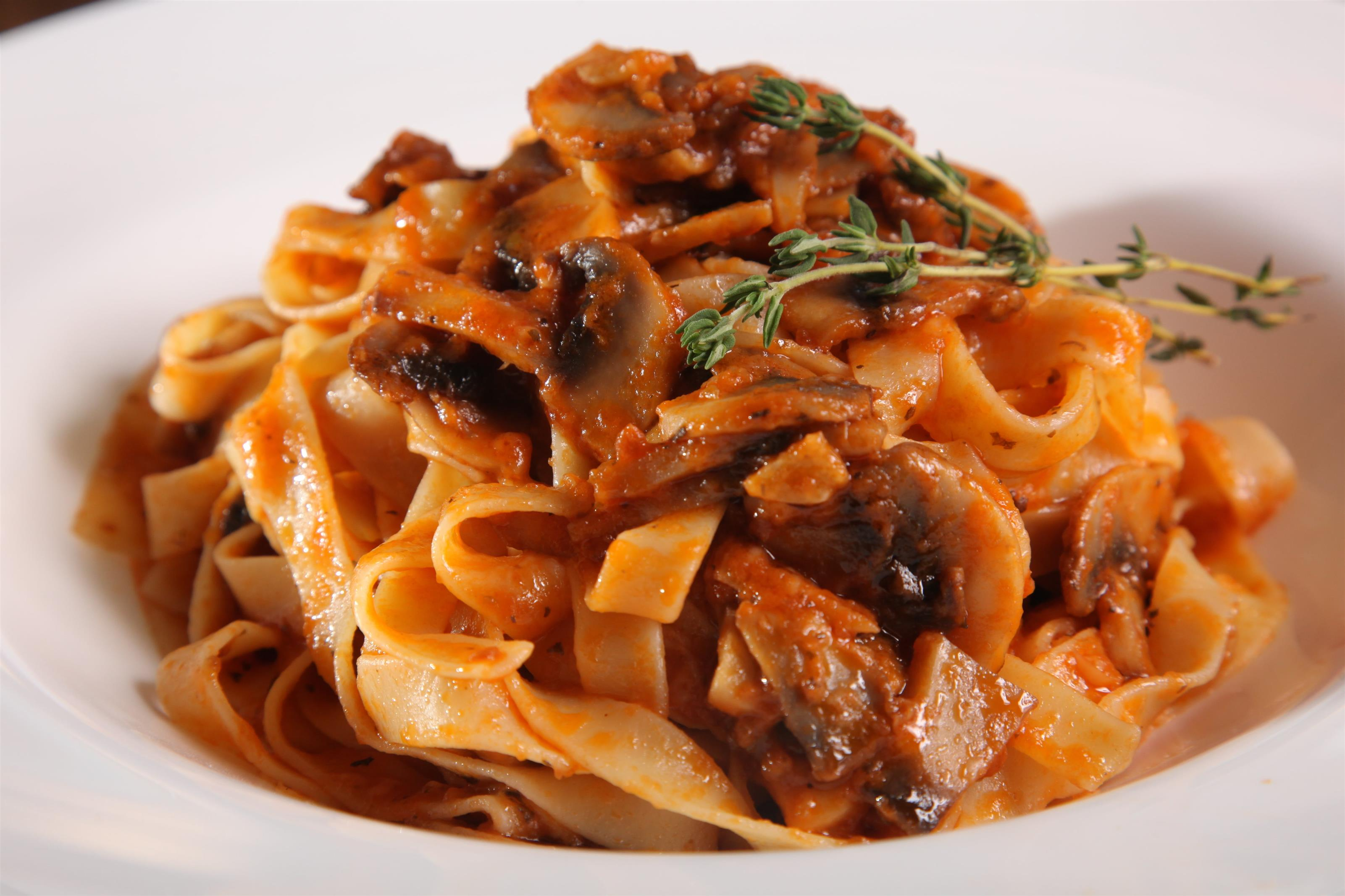 Fettuccine with red sauce and mushrooms in white dish.