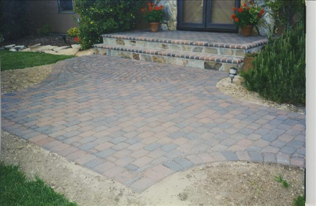 brick walkway in front of house with two steps in front of the door