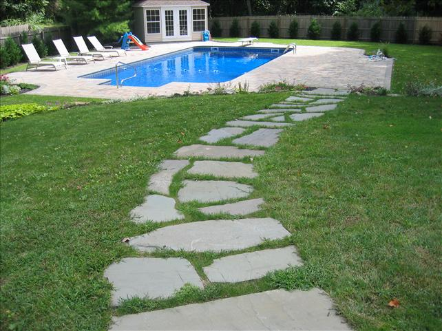 stone walkway in grass leading to pool area