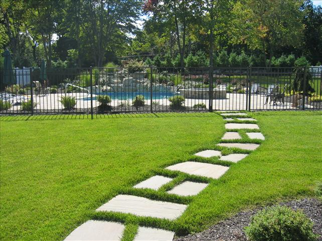 stone walkway in grass leading to a gated pool area