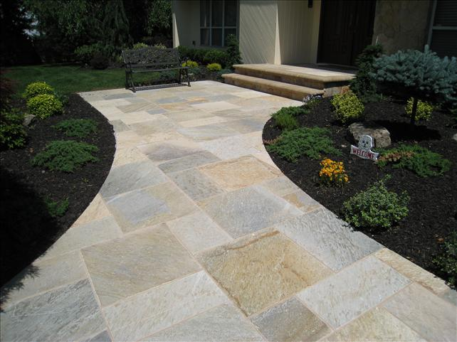 large square stone walkway to front door with small plants on the side