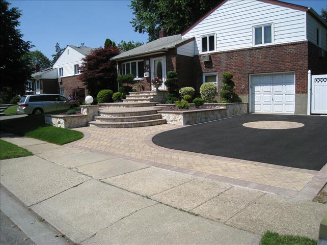 paved driveway with brick walkway and steps to front door