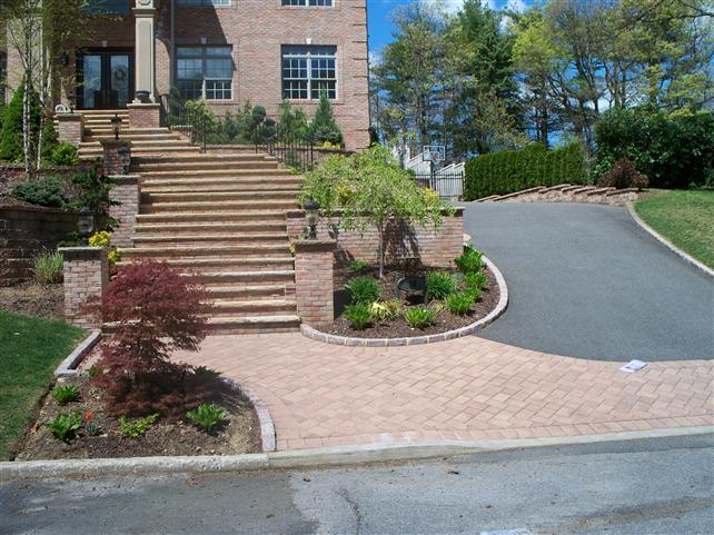 brick front walkway with paved driveway and many stairs leading to front door.
