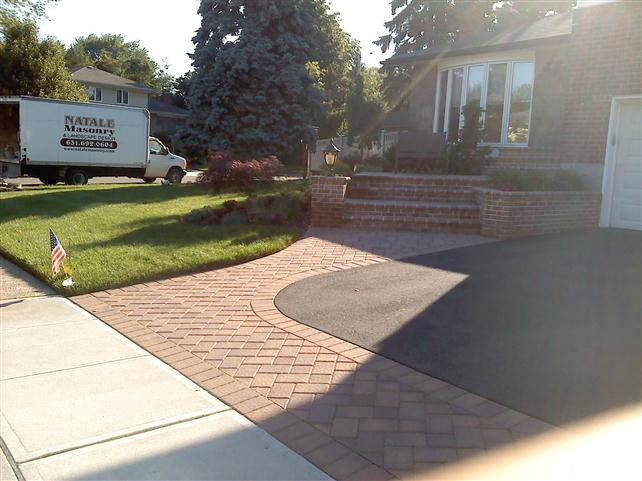 brick walkway around paved drive way with brick steps leading to front door