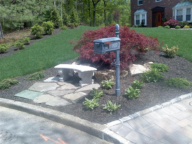 mailbox in soil with stone bench