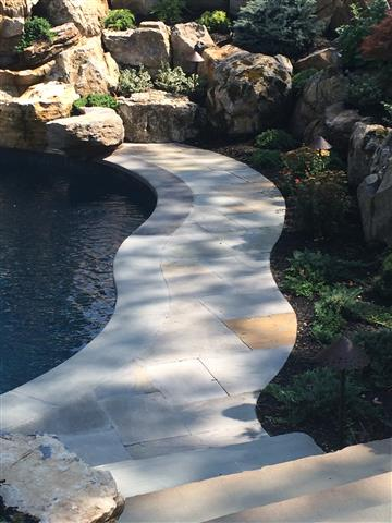 Stone walkway in back yard bordering pool