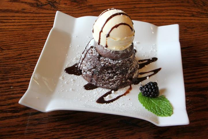 Chocolate cake topped with a scoop of ice cream