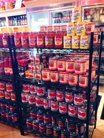 Interior shot of Primavera Italian Specialties with a stand with cans of tomato sauces