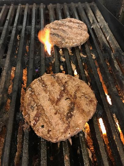 two burgers on a grill