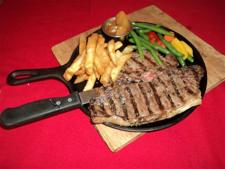 grilled menu item meat with fries and vegetables on the side