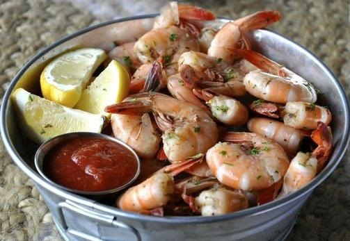 metal bucket filled with cooked shrimp, dipping sauce and lemon wedges