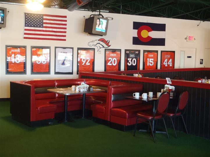 Dining area of restaurant with jersey's along with the American flag and Colorado flag