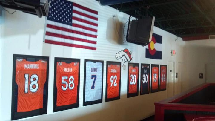 American flag along with the Dever Broncos logo, a television, and Colorado flag